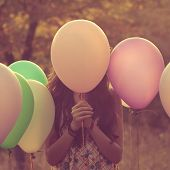 pic of shy girl  - Hipster Girl hiding behind the balloons outdoors - JPG