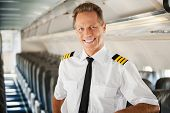 picture of cabin crew  - Confident male pilot in uniform leaning at the passenger seat and smiling while standing inside of the airplane - JPG