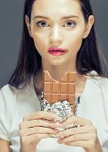 stock photo of bulimic  - cute young female with chocolate close up eating - JPG