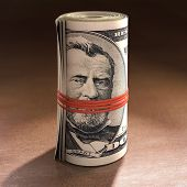 stock photo of gag  - Money roll with elastic gagging the mouth of Ulysses S - JPG