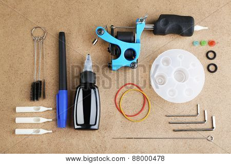 Tattoo machine and tattoo Supplies, on wooden background