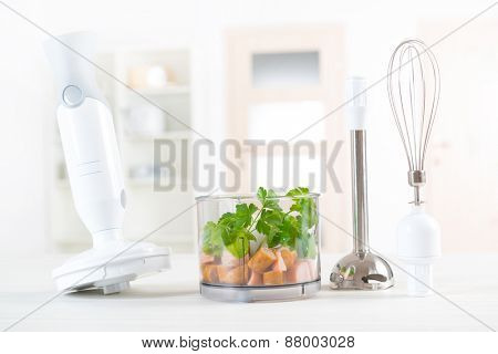 Preparing food with hand blender, green leaves and meat inside