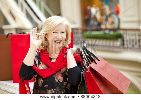 Mature happy blonde woman with shopping bags