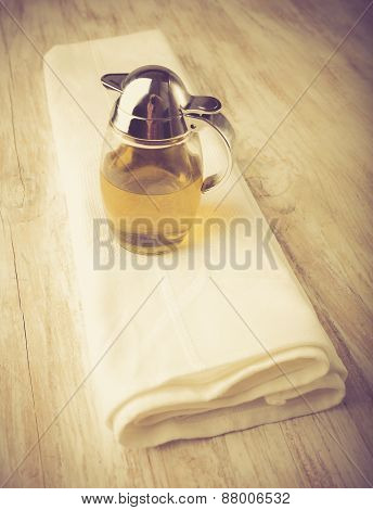 Vintage Photo Of Olive Oil In A Jug On A White Wood