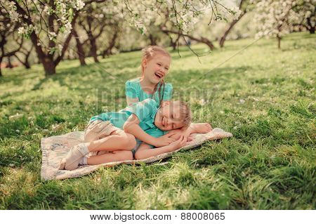 happy siblings playing in spring apple garden