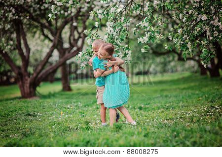 happy siblings playing in spring blooming apple garden
