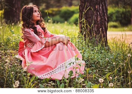 child girl dressed as fairytale princess in summer forest