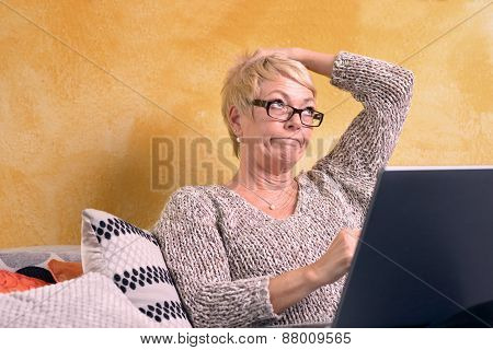Thoughtful Woman Sitting At Sofa With Laptop
