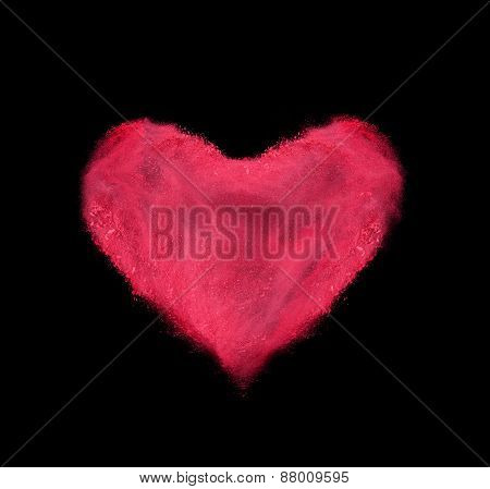 heart made of red powder explosion on black background