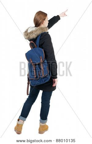 Back view of  pointing young women in parka with backpack.  Young girl gesture. Rear view people collection.  backside view of person.  Isolated over white background.