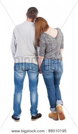 Back view of young embracing couple (man and woman) hug and look into the distance. beautiful friendly girl and guy together. backside view of person.  Isolated over white background.