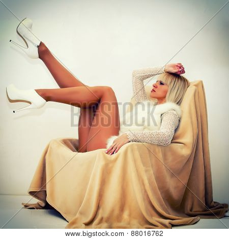 Sexy Blond Woman Lying On Armchair
