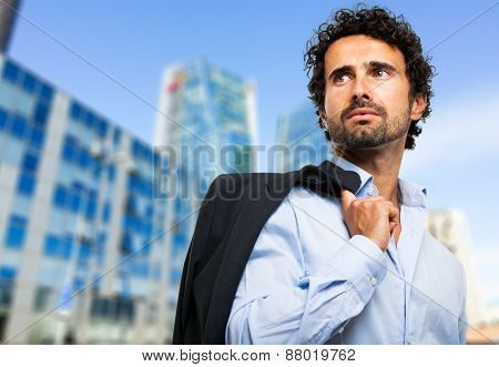 Confident young businessman outdoor holding his jacket