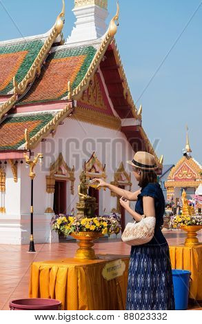 Young woman with her descendant are pouring water onto Buddha image