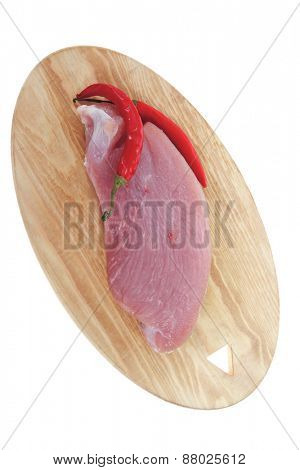 raw fresh turkey meat steak fillet cuts on wooden board with red hot chili pepper isolated over white background