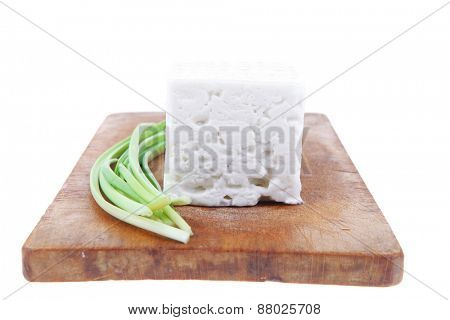 diet food : greek feta white cheese served on wooden plate isolated over white background