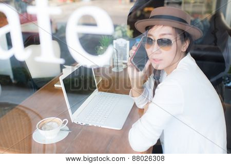 Asian Woman Drinking Coffee And Using Computer In Cafe. Photo Filter Effect And Selective Focus.