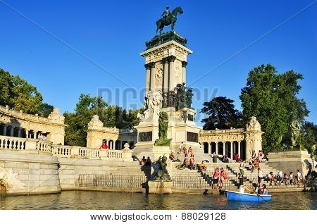 MADRID, SPAIN - AUGUST 10: People sitting at the Monument to Alfonso XII in Parque del Retiro on August 10, 2014 in Madrid, Spain. This public park is the main park and the most popular in the city