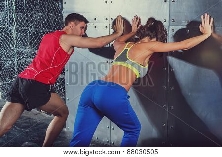 Handsome guy and beautiful young girl doing some exercises against the wall together.