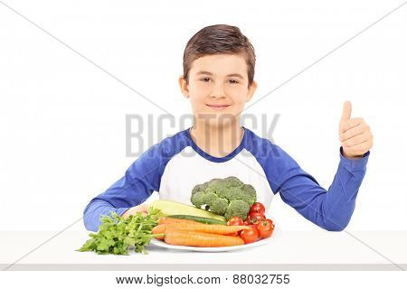 Little kid sitting on a table with a plate full of fresh vegetables and giving a thumb up isolated on white background