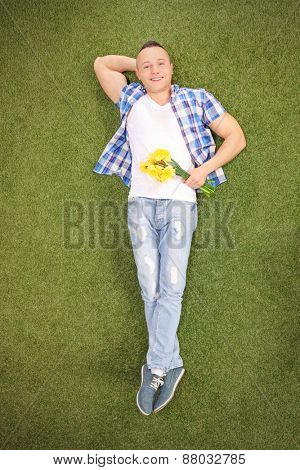 Full length vertical shot of a relaxed young guy lying on grass in a meadow, holding a bunch of yellow tulips and looking at the camera
