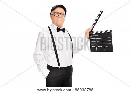 Studio shot of an artistic senior man holding a clapperboard and looking at the camera isolated on white background