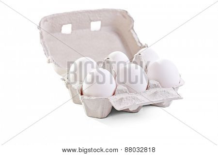 Studio shot of six white eggs in a cardboard egg box isolated on white background