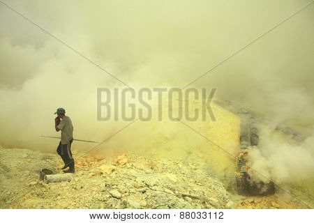 KAWAH IJEN, INDONESIA - AUGUST 10, 2011: Miner collects sulphur in the fumes of toxic volcanic gas at the sulphur mines in the crater of the active volcano of Kawah Ijen, East Java, Indonesia.