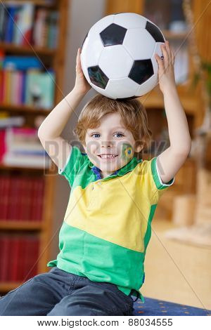 Little Funny Kid Boy Playing With A Football At Home