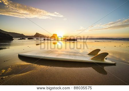 Silhouette of a surfboard at the beach with reflection