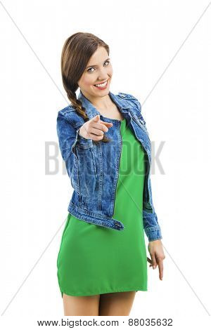 Beautiful woman smiling and pointing to you, isolated over a white background
