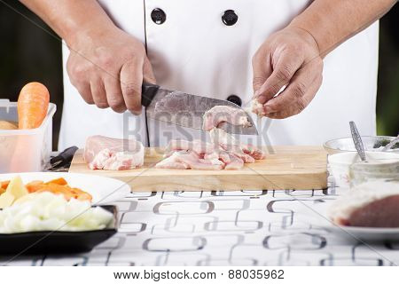 Close Up Of Hand's Chef Cutting Raw Pork On Wooden Board
