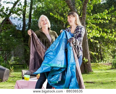 Cheerful mother and daughter assembling tent in park at campsite