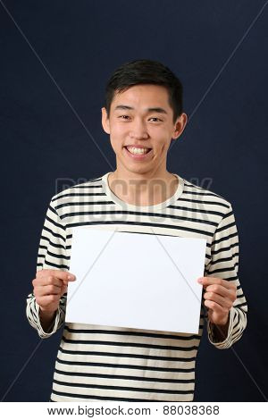 Young Asian man showing white copy space page and looking at camera
