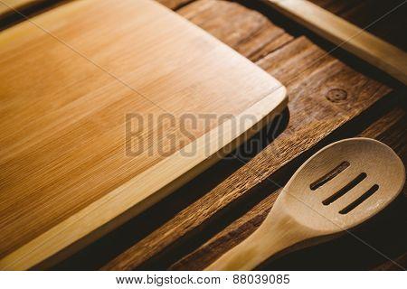 Chopping board with wooden utensils shot in studio