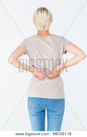 Blonde woman having a back ache and holding her back on white background