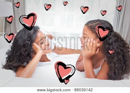 Red Hearts against smiling mother and daughter posing together on bed