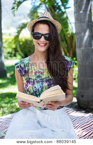 Smiling beautiful brunette sitting and reading a book with palm tree behind her