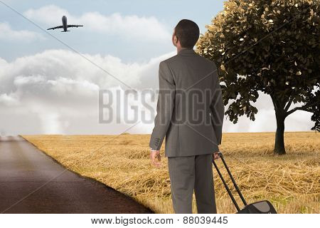 Young businessman standing with suitcase against road leading out to the horizon