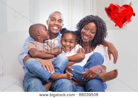 Happy family posing on the couch together against heart