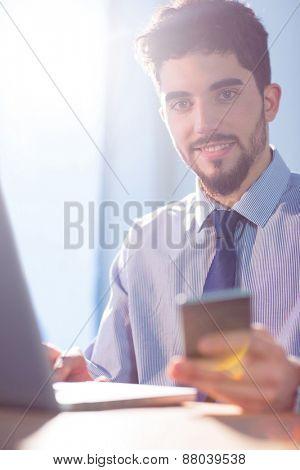 Businessman using laptop at desk shot in studio