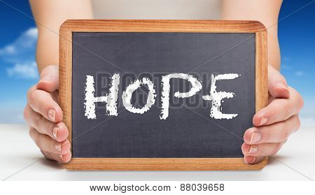 The word hope and females hands showing black board against bright blue sky with clouds