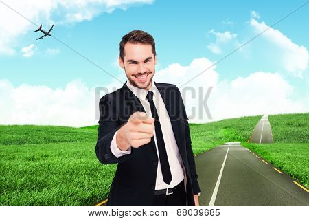 Happy businessman pointing at camera against road leading out to the horizon