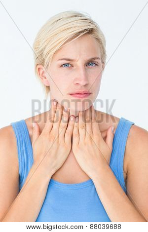 Woman with throat pain looking at camera on white background