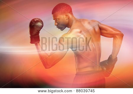 Muscular boxer against sunrise sky