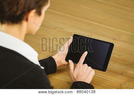 Businesswoman using tablet at desk shot in studio