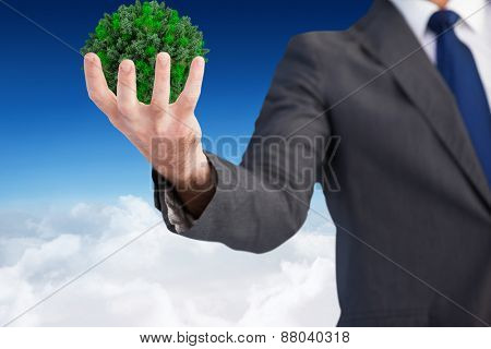 Businessman presenting with his hands against blue sky over clouds