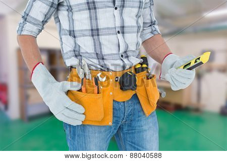 Technician holding spirit level over white background against workshop