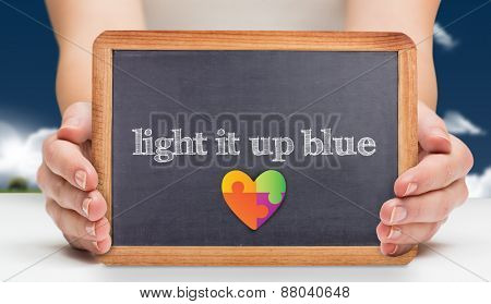 The word light it up blue and females hands showing black board against field and sky
