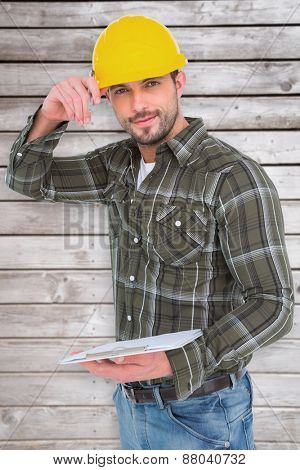 Smiling handyman writing on clipboard against digitally generated grey wooden planks